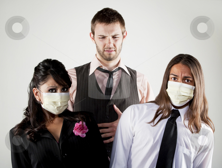 Sick man and worried coworkers in masks stock photo, Tall man with stomach upset and coworkers wearing masks by Scott Griessel