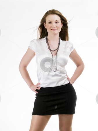 Young woman in black skirt and white blouse stock photo, Young caucasian woman with arms on hips by Jeff Cleveland