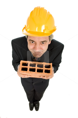 Holding a brick stock photo, Mature worker holding a brick, isolated on white by Rui Vale de Sousa