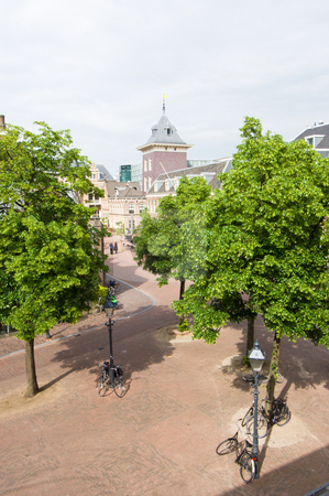 Haarlem city center stock photo, A hotel room view on Haarlem's empty streets in the city center, with parked bikes, lush trees, and the new court house in the distance by Corepics VOF