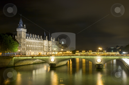 Parisian Nights stock photo, A nightly view over the river Seine in Paris, with it's nicely lit bridges and historic buildings. A police van is just crossing the intersection on the left, where the light jumps from green to red. by Corepics VOF