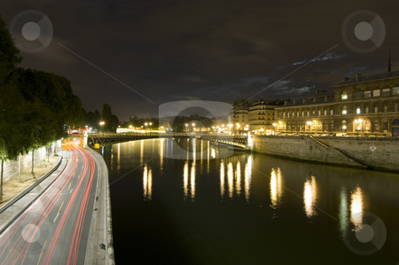 Parisian Nights stock photo, A nightly view over the Seine with it's many bridges, and ring road, close to Ile de la Cite. The moon shines through a break in the clouds by Corepics VOF