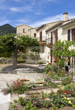 Rural garden stock photo, The colorful feel of a Classic French residential area, with herbes, flowers, trees, balconies and old houses. by Corepics VOF