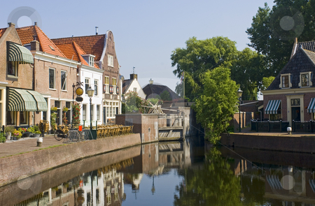 The Dutch Village of Spaarndam stock photo, The old 16th century (1571) village of Spaarndam, the Netherlands, with the old inner harbour, it's sluices and locks, the fishermans' houses, currently a quaint town with a terrace, bikes and a very quiet atmosphere by Corepics VOF
