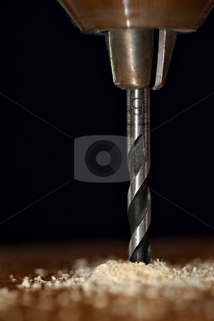 Drill bit stock photo, Detail of  drill bit in a piece of wood with dark background by Juraj Kovacik