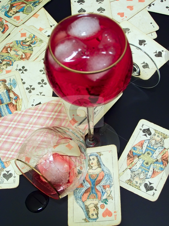 Broken glass, wine with ice and cards stock photo, Wineglass with the red and plaing cards on the table with broken glass by Sergej Razvodovskij