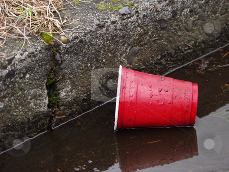 Littering stock photo, A red plastic cup lays in the gutter, dirty and discarded. by Robert Gebbie