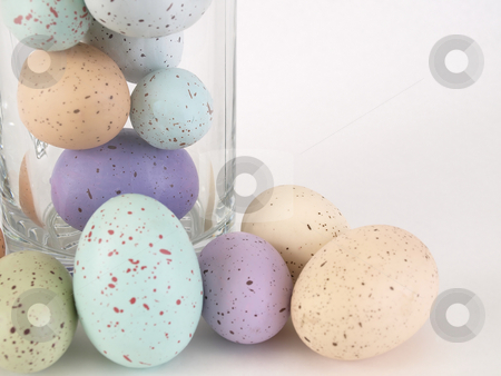 Pastel Eggs on Display stock photo, A group of pastel colored flecked eggs. Some are loose and some contained in a glass container. Over white. by Robert Gebbie