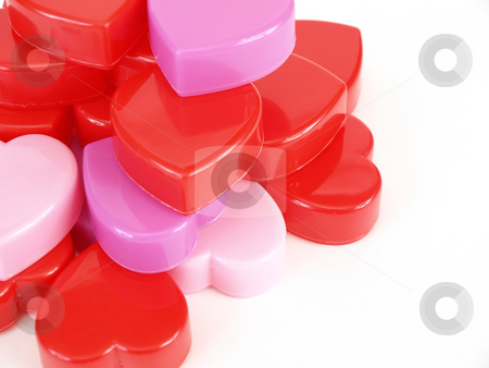 Heart Stack stock photo, Plastic heart shapes in red, pink and lavendar, stacked up over a white background. by Robert Gebbie