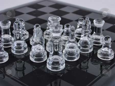 King and his Court stock photo, Clear glass chess pieces on an etched glass chess board. over white. by Robert Gebbie