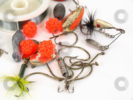Tackle and Hooks stock photo, Various fishing lures, bait and a spool of line over a white background. by Robert Gebbie