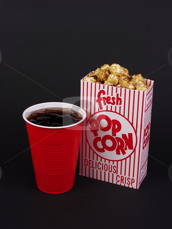 Movie Snacks stock photo, A box of caramel corn and a red cup of soda on a black background. by Robert Gebbie