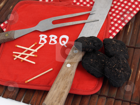 Barbecuing Utensils stock photo, Items used for a Barbeque, including charcoal, wooden matches and a bright red pot holder. by Robert Gebbie
