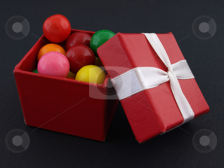Gumball Gift stock photo, Small red giftbox full of colorful gumballs. Isolated against a black background by Robert Gebbie