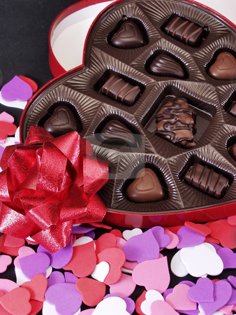 Hearts stock photo, Multi colored heart cut outs spilled around a heart shaped box of chocolate candy. A shiny red bow completes the setting. by Robert Gebbie