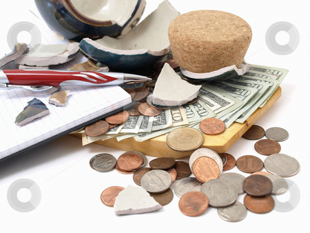 Can't Afford It stock photo, An open ledger and pen next to a broken ceramic bank on a pile of loose United States coins and currency. by Robert Gebbie