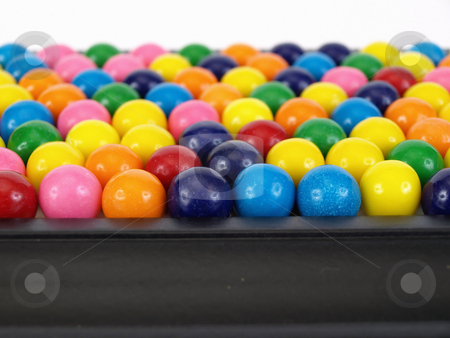 Gumball Horizon stock photo, A colorful variety of gumballs in a close but random pattern. Horizon view over a white background. by Robert Gebbie