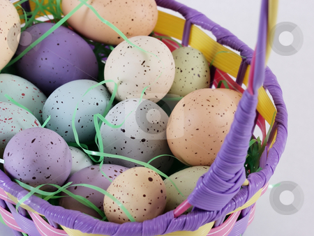 Easter Eggs in a basket stock photo, Multi colored pastel speckled eggs in an Easter basket with Easter grass. by Robert Gebbie