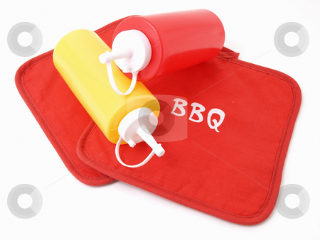 Ready for the Cookout stock photo, Ketchup and Mustard squeeze bottles laying on two red potholders. by Robert Gebbie