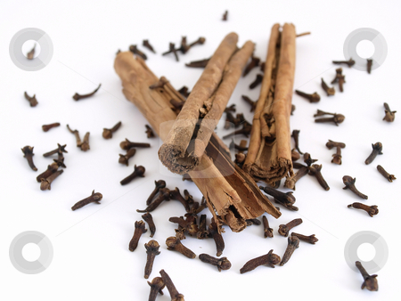 Cinnamon and Cloves stock photo, Cinnamon sticks on a spread of whole cloves. Studio isolated over white. by Robert Gebbie