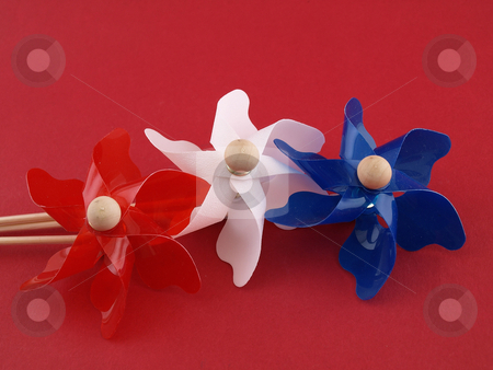 July Pinwheels stock photo, Red, white and blue plastic pin-wheels against a muted red background. by Robert Gebbie