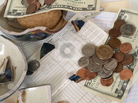 Broke the Bank stock photo, US Currency and broken ceramic pieces from a bank lay over empty ledger books. by Robert Gebbie