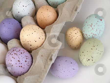 Pastel Easter Dozen stock photo, A cardboard container holding pastel flecked Easter eggs sits open, a few eggs loose on the counter. Over white. by Robert Gebbie