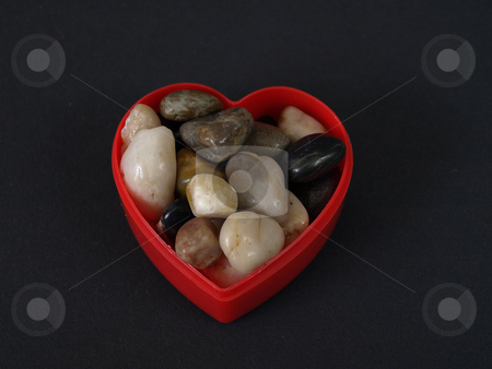 Stone Filled Heart stock photo, A red plastic heart shaped container holds a variety of polished decorative stones. Over black. by Robert Gebbie
