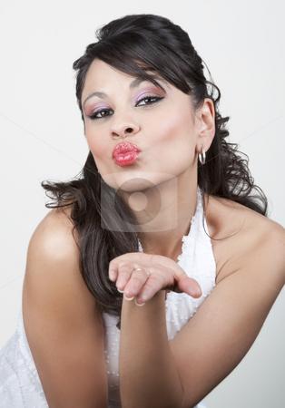 Pretty Hispanic Woman Blowing Kiss stock photo, Pretty Hispanic woman in a white top blowing kiss by Scott Griessel