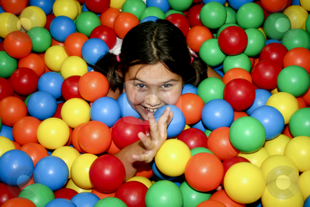 Girl playing stock photo, Gilr covered with clored balls by Jos?