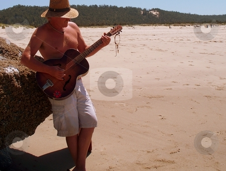 Man on Beach with guitar stock photo, Man Playing Guitar on the sunny beach by Carol Grimes