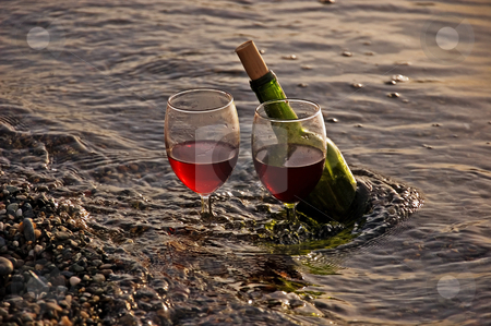 Two Glasses Red Wine and Bottle in Ocean stock photo, This is a photo of 2 glasses of red wine and the wine bottle at the shore of a beach with waves. by Valerie Garner