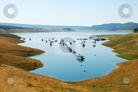 Houseboats on Lake stock photo, A line of houseboats on the New Melones Lake in California. by Denis Radovanovic