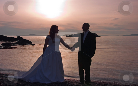 Silhouette of Bride & Groom Holding Hands On Beach stock photo, This lovely photo is a silhouette of a bride and groom holding hands at sunset on a beach overlooking the ocean. by Valerie Garner