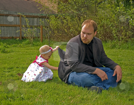 Toddler Girl is Getting Into Daddy's Pocket stock photo, This adorable little toddler girl is lifting up daddy's jacket in order to try to get something out of his pocket. by Valerie Garner