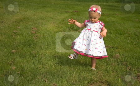 Toddler High Stepping in the Grass stock photo, This cute toddler girl is stepping high in the long grass, not liking it touching her legs. by Valerie Garner