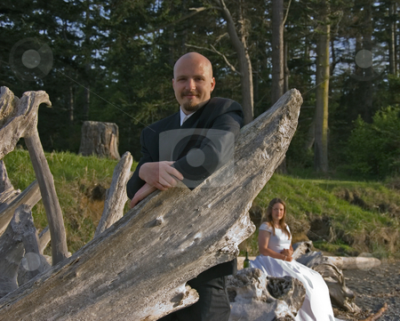 Groom Leaning on Diftwood  stock photo, This smiling groom is leaning on some driftwood while his bride is sitting beautifully in the background. by Valerie Garner