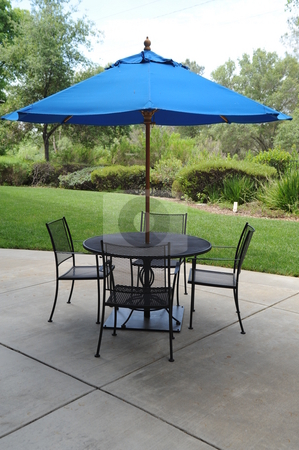 Wrought Iron Table With Umbrella stock photo, Blue umbrella, table and chairs on a patio in a graden setting by Lynn Bendickson