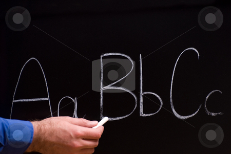 Primary School stock photo, Closeup view of a teacher holding some chalk and writing basic letters on a blackboard by Richard Nelson