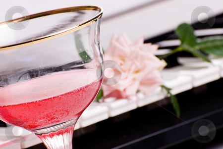 Romantic Music stock photo, Focus on wine glass and an electronic piano in the background by Richard Nelson