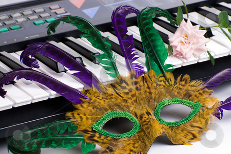 Musical Party stock photo, Closeup view of a feathered mask and a pink rose resting on an electronic keyboard instrument by Richard Nelson