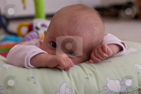 Playtime stock photo, Caucasian baby girl playing on her colorful playmat. by Mariusz Jurgielewicz