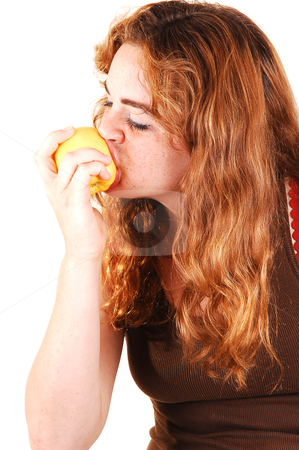 This apple is good. stock photo, Pretty girl with long bright red hair eating an yellow apple and really enjoying the fruit. by Horst Petzold