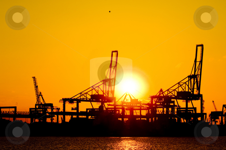 Cranes at sunset stock photo, Silhouette of huge commercial harbor against a setting sun on a summer afternoon by Corepics VOF