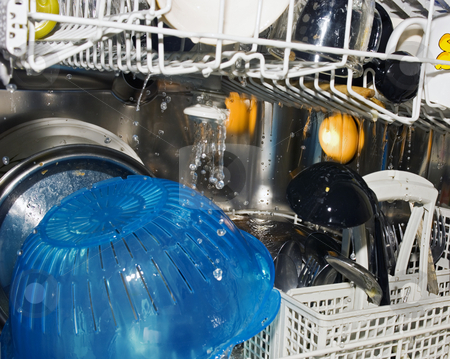 Dishwashwer at work stock photo, A dishwasher at work, cleaning dirty pans, pots, cutlery and other dishware by Corepics VOF