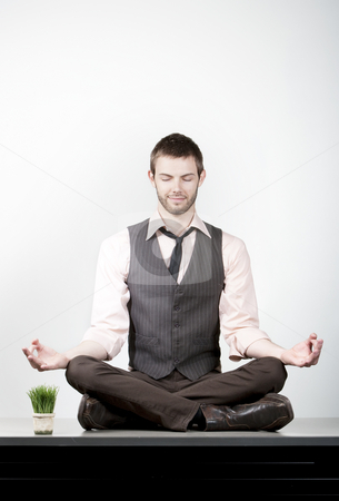 Handsome Young Businessman Meditating on Desk stock photo, Handsome yopung businessman meditating on office desk by Scott Griessel