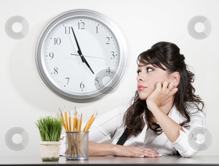 Bored woman at the end of the day stock photo, Bored woman at her desk at the end of the day by Scott Griessel