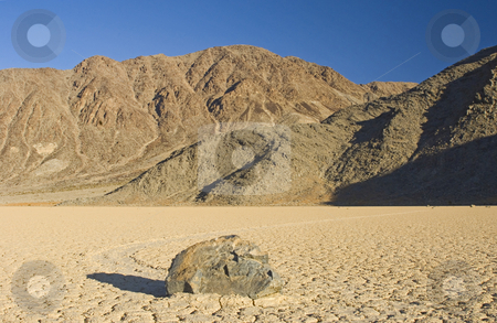 Race Track Playa stock photo, The phenomenon of the moving rocks at Death Valley Race Track Playa. The setting sun casts a shadow over the near by rock, still basking the mountains in the background in a warm glow by Corepics VOF