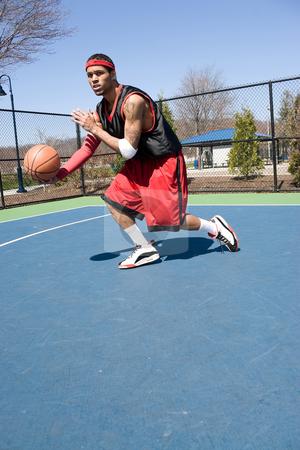 Basketball Player Dribbling stock photo, A young basketball player driving to the hoop demonstrating his ball handling skills. by Todd Arena