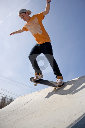 Skateboarder on a Ramp stock photo, A young man skateboarding down a ramp at the skate park. by Todd Arena